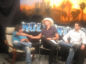 """PHOTO CAPTION: Coldwater Canyon Band frontman Howie Vaughn and fellow band member Brandon Fisher being interviewed by former Howard Stern entertainment reporter Gary Garver for an upcoming episode of """"Gary Garver Live."""""""